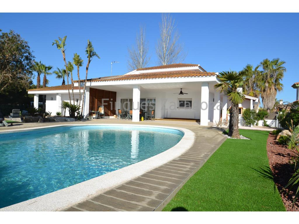 The villa is located in Riumar - Ebro Delta, a few meters from the Promenade, the beach and the harbour. Riumar is a small urbanization with 1.000 houses aprox, surrounded by the Natural Park.The villa is built on a 1390 m² parcel, in which there is a large garden that combines tropical and native trees, artificial grass area and a large swimming pool with barbecue area and terrace.The villa has two floors, totaling 298 m². On the ground level we have access directly from the garden to a hallway distributor that gives access to the living room, at the bottom of this, we find the dining room, which at the same time gives access to the kitchen and through a staircase you access the garage .From the hallway of the entrance we also have access to a bathroom for the guests, the laundry room and the three double bedrooms on the ground floor; Two of them with fitted wardrobes and private bathroom.In the living room of the same floor there is a staircase leading to the first floor where we find a large room with access to the terrace and a smaller one with a private bathroom.The house has heating in all rooms.