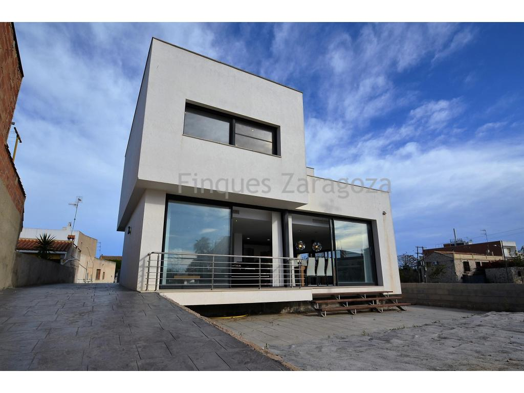 Design house in Deltebre, located in the heart of the Delta del Ebro Natural Park, a few meters from the Ebro river and 10 minutes from the beaches of Riumar and Ampolla.The house is located on a plot of 2,271 m2 and occupies a constructed area of 242 m2. On the ground floor we find a garage, where from  you can directly access the interior of the house. On the same floor we find a large kitchen type office with island, dining room and living room in the southern part of the house. In the northeast there is a bathroom with shower for guests and two bedrooms. On the first floor there is an office with views to the back of the house and the master suite with dressing room and 2 terraces.In the basement there are two more rooms that can be used as a game room for children and a cellar.The house is mainly south facing and has natural light all the day. Top quality finishes both inside and outside the estate.