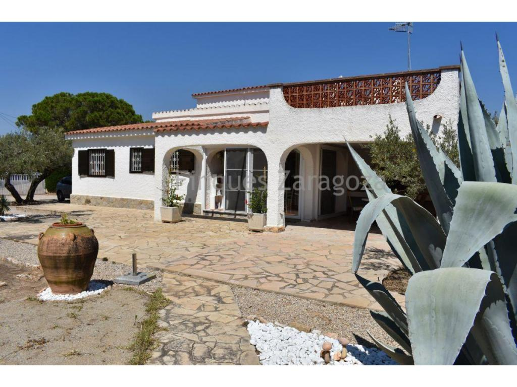 Villa located 350m. from the beach and 2.5km. from town.Construction area: 155m². Plot of 1154m².Distribution:GROUND FLOOR: living room-kitchen-equipped with fireplace, 3 double bedrooms with fitted wardrobes, 1 bathroom, covered terrace, office-laundry room and exterior staircase.FIRST FLOOR: access staircase, one bedroom suite with a bathroom with showerConstruction of good quality, technical premises, storage room, parking area. Porch with barbecue. Furnished.Heating with electric radiators, ceiling fans of all units.Yard.