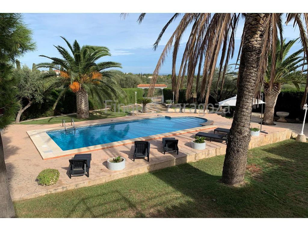 Unique for its incredible pool and garden area. For sale in Alcanar Playa, South Costa Dorada.It has an area of 150m² which are distributed in 3 double bedrooms, one with its own bathroom, it has 2 more bathrooms with shower, a large living room with fireplace, a large separate kitchen and a fully glazed terrace which can be enjoyed both in summer and winter. There is reversible air conditioning in 2 bedrooms and in the lounge-dining room. It has a private garage of about 20m², storage room, laundry room, a large private swimming pool, a magnificent garden and barbecue. Plot of 1350m².